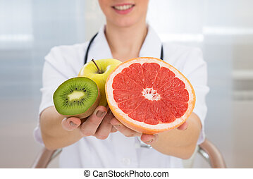 Dietician Holding Fresh Sliced Fruits - Close-up Of Happy...
