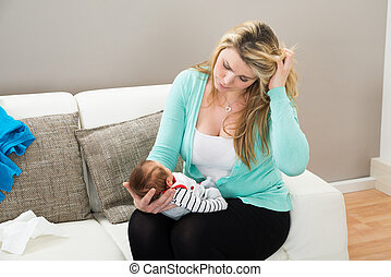 Mother With The Baby - Stressed Mother On Sofa With Carrying...
