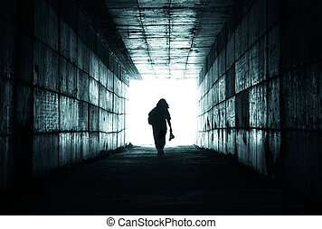 Light at End of Tunnel - silhouette of a person reaching the...
