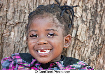 african child with braids having a toothy smile