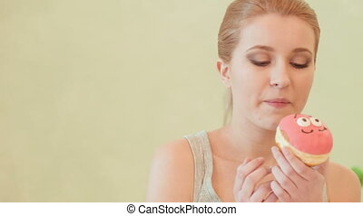 Young woman eating doughnut - finally pleasure. Selective...