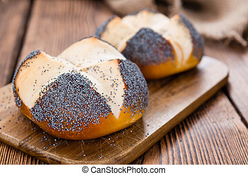 Homemade Pretzel Roll with Poppyseed on rustic wooden...