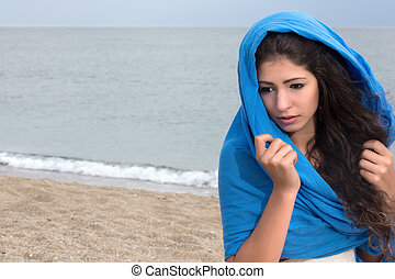 Blue headscarf - Windy day on the beach with a girl wrapped...