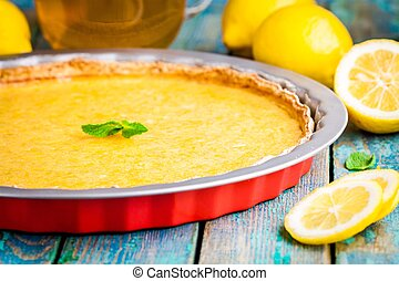 lemon tart in baking dish on rustic blue table