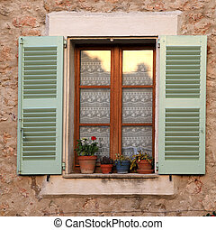 rustic window with green wood shutters in stone rural house, Pro