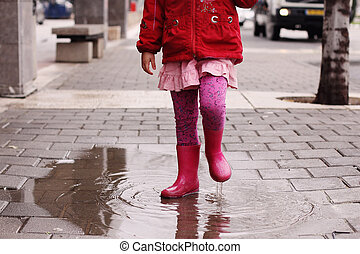 Adorable 4 years old girl at rainy day in springtime