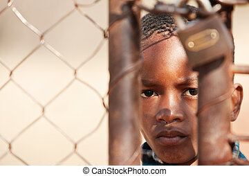 stolen life - african child locked behind a metallic gate