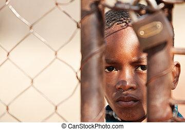 stolen life - african child locked behind a metallic gate