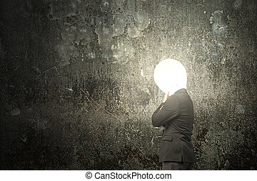 Thinking businessman with lamp head illuminated dark mottled...
