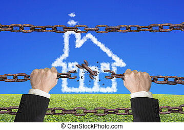 Rusty iron chains broken off by hands with house clouds