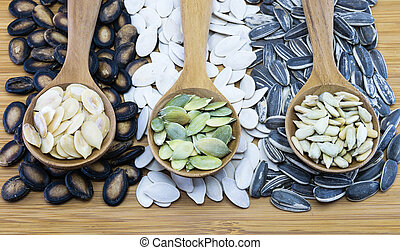 Variety of edible seeds in wood spoon on wood background -...