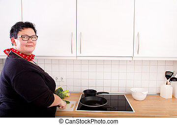 Woman cutting and frying cucumber - Mature overweight woman...