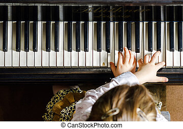 Cute little girl playing grand piano in music school,...