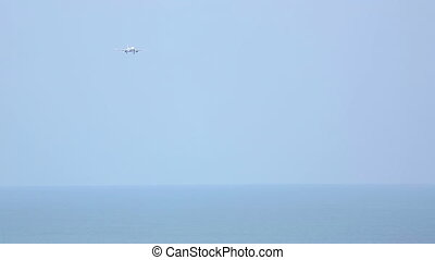 Final approach over ocean - Jet airplane approaching over...