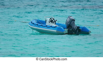 Boat on the waves - Dinghy with engine rocking on the waves...