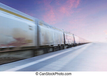Freight train in blurred motion on purple and blue evening...