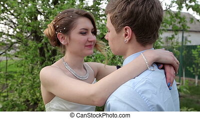 bride groom gently embraces the neck in the spring garden
