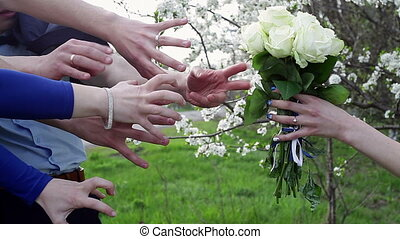 bride holds a bouquet and a lot of hands trying to grab it