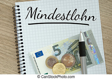 Minimum Wage - Writing pad with money and the german word...