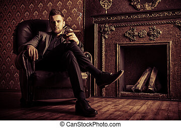 richness - Elegant man in a suit with glass of beverage and...
