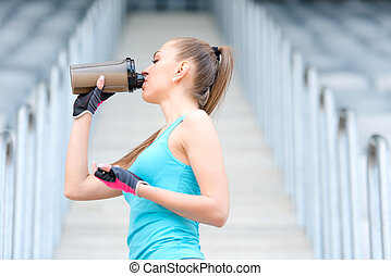 Portrait of healthy fitness girl drinking protein shake....