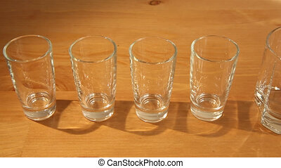 Small glasses and a whiskey one - Sliding over a row of...