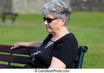 Older lady relaxes outside on a park bench