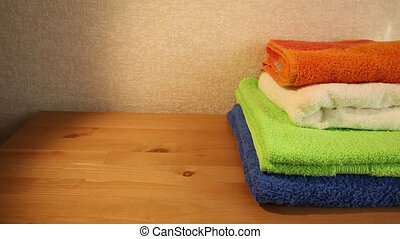 Four towels on a table - Sliding view of a pile of four...