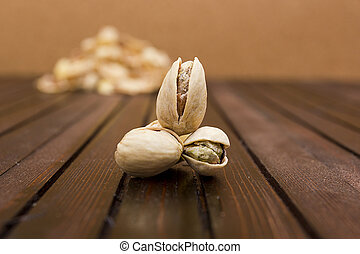 Pistachios on a wooden surface in the background slide of...