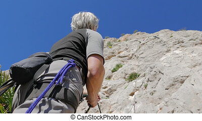 Caucasian person rock climbing - Caucasian senior securing...
