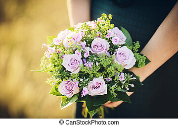 bride holding her bouquet of purple flowers on her wedding...