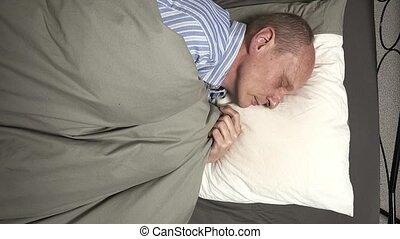 Timelapse of aMan in pajamas or jammies sleeping in bed