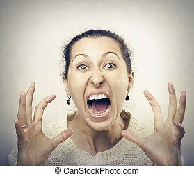 Furious woman screaming. Front view of furious brunette...
