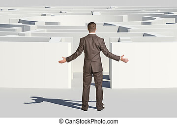 Businessman throwing up his hands in front of labyrinth,...