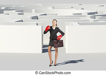 Businesswoman in boxer gloves looking at camera -...