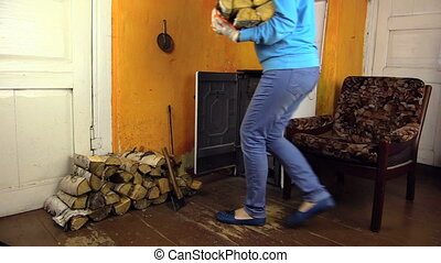 woman bring wood furnace - young countrywoman bring in arms...