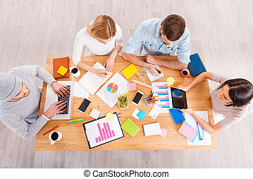 Concentrated at work. Top view of group of business people in smart casual wear working together while sitting at the wooden desk