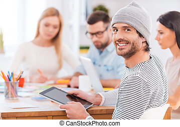 Confident in his team. Handsome young man looking over shoulder and smiling while holding digital tablet and sitting together with his colleagues at the wooden table in office