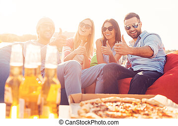 We love pizza and beer Four young cheerful people showing...