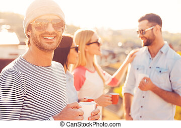 Coffee time. Handsome young man in hat holding coffee cup and smiling while standing near his friends on the roof terrace