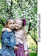 Little girls playing in spring park tree outdoor
