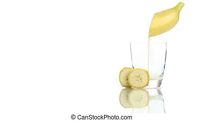 banana juice poured into the glass isolated on white...