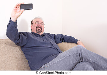Middle-aged man sitting and taking selfie pictures -...