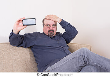 Vain man taking a selfie on his smartphone checking his hair...
