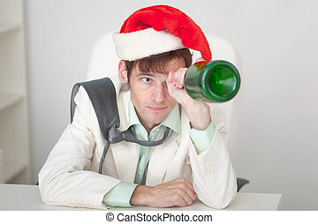 Amusing guy in Christmas cap with bottle in a hand