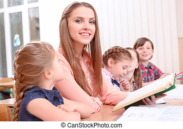 Young teacher reading to pupils
