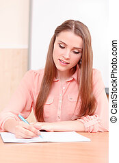 Youthful woman writing in copy book
