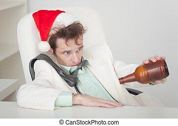 Drunken person in Christmas cap with bottle in a hand