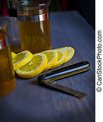 Tea, lemon and a knife on woodboard - Tea, lemon and a knife