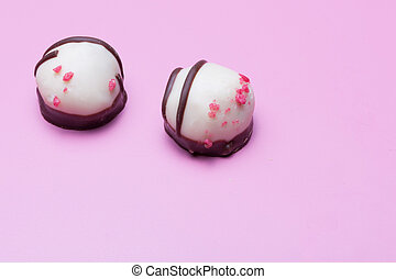 confections - two sweet pralines on a violet background